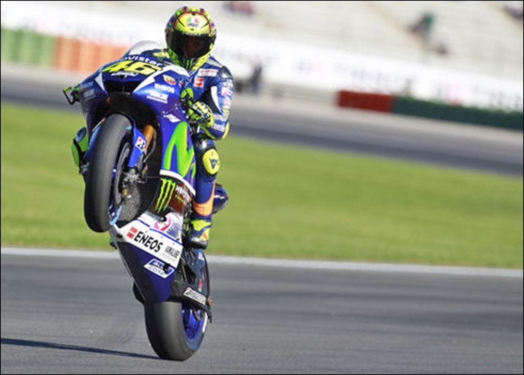 Valentino Rossi riding a wheely on racing motorcycle